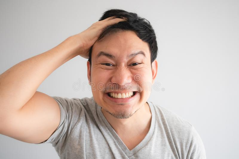 Very happy funny face of man with a big innocent smile in grey t-shirt royalty free stock photo