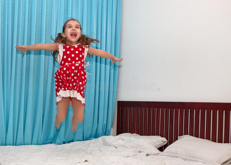 Very happy girl jumping on the bed stock photography