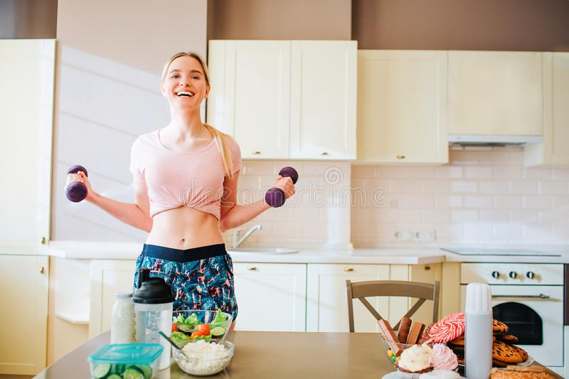 Very happy joyful young woman holding dumbbells in hands and exercising. Smiling and full of happiness. Alone in kitchen royalty free stock image