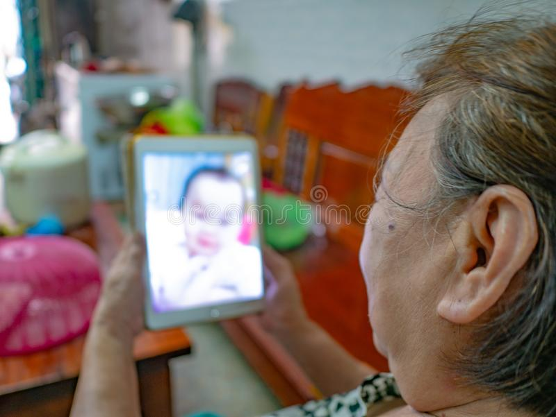 Very happy Old asian women Look at the tablet in her house stock photo