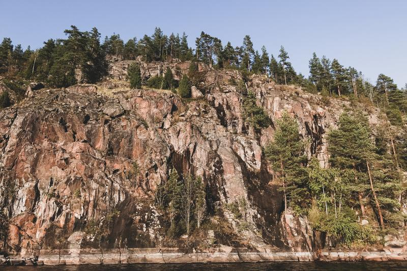 Very high rocky lake shore with a rare forest. Karelia stock image