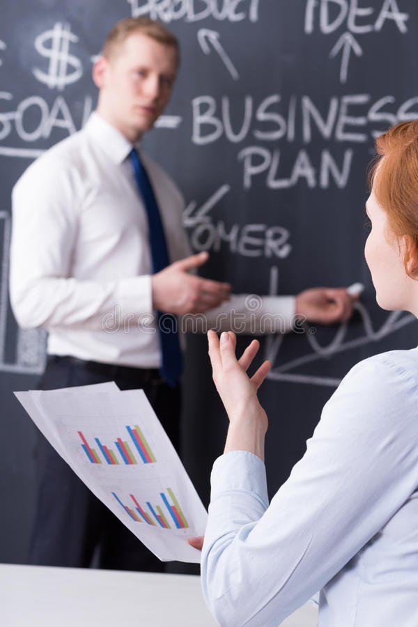 Very important business presentation. Co-workers during business presentation, blackboard with a business plan drawn in the background stock photos