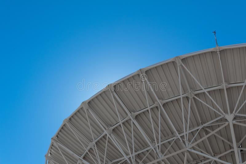 Very Large Array backlit sweep of radio astronomy observatory dish in clear sky, science technology space. Horizontal aspect stock photography
