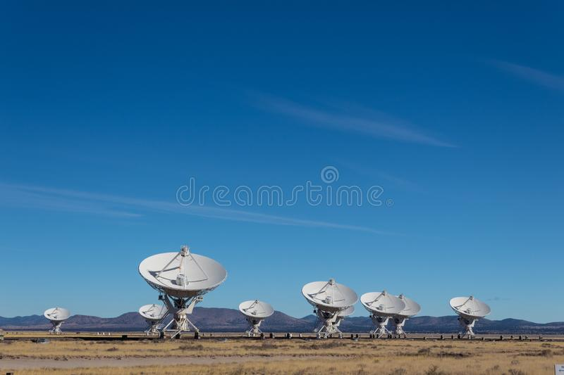 Very Large Array Distant view of numerous dish antennas pointing toward a blue sky, science technology space exploration. Horizontal aspect stock images