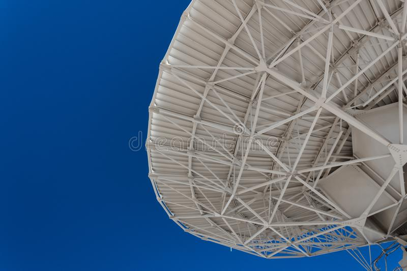 Very Large Array engineering understructure of a very large radio telescope dish against a vivid blue sky, copy space, science tec. Hnology, horizontal aspect stock photography
