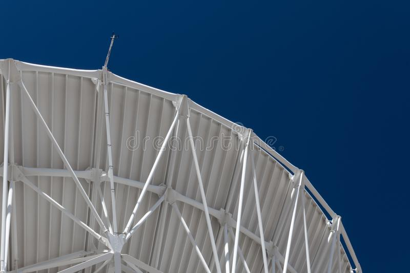 Very Large Array graceful arch of a large radio telescope dish against blue sky, science engineering. Horizontal aspect royalty free stock photos