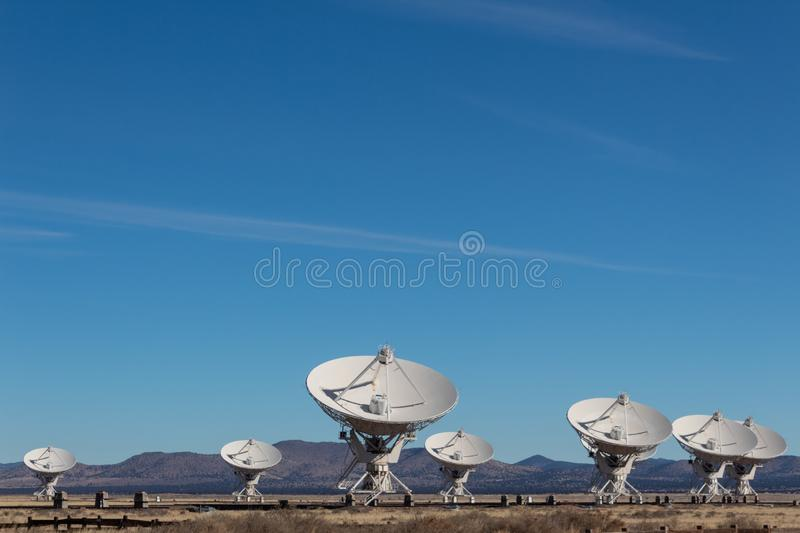 Very Large Array grouping of radio antenna dishes in New Mexico desert, blue sky. Copy space, horizontal aspect stock photography