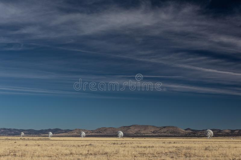 Very Large Array line of radio astronomy observatory telescopes in the New Mexico desert, copy space in blue sky. Horizontal aspect royalty free stock photography