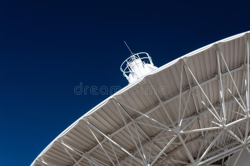 Very Large Array radio telescope dish pointing into a deep blue sky, science technology. Horizontal aspect royalty free stock image