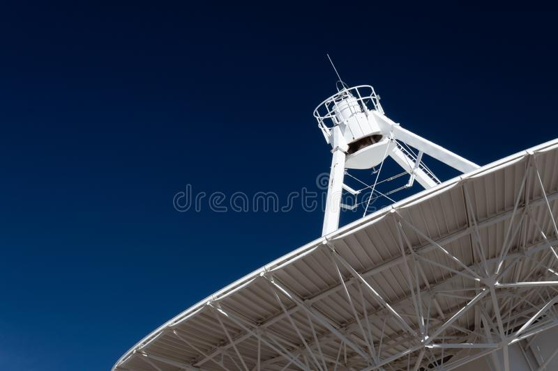 Very Large Array radio telescope pointing into space, white dish against a deep blue sky, space technology. Horizontal aspect stock images