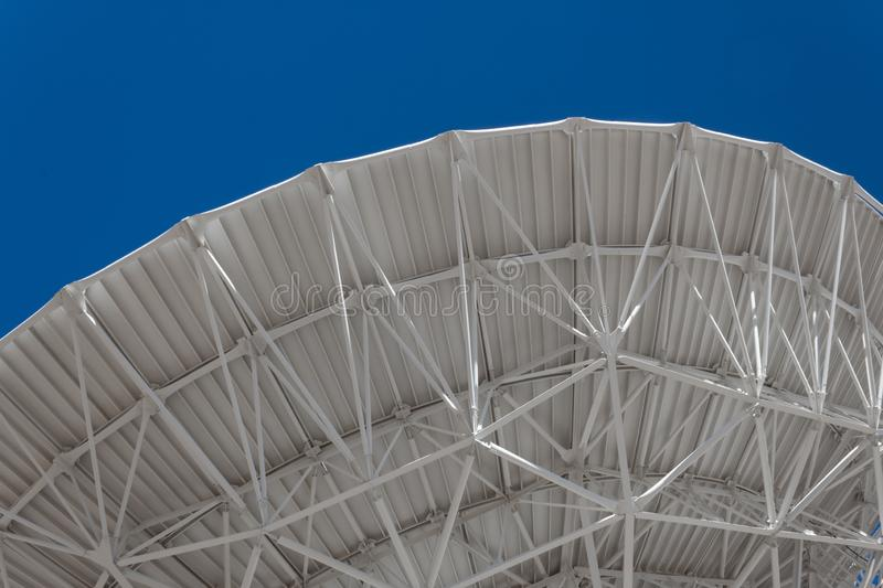 Very Large Array sweeping arch showing understructure of a large dish telescope against a blue sky, engineering and technology. Horizontal aspect stock photos