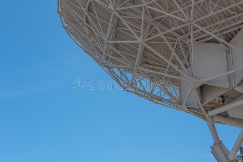 Very Large Array trusses show engineering on large dish against blue sky, backlit, science technology space. Horizontal aspect royalty free stock image