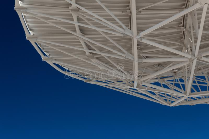 Very Large Array trusses on the underside of a radio astronomy observatory dish with blue sky beneath, creative copy space. Horizontal aspect stock photos