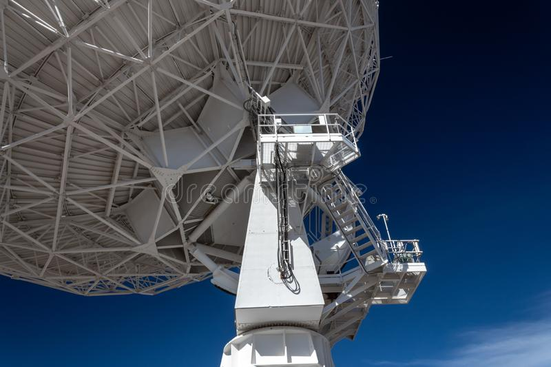 Very Large Array upright and trusses under radio astronomy observatory dish against blue sky, science technology engineering. Horizontal aspect stock image