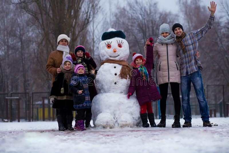 A very large family of three generations: grandmother, father, mother and daughters sculpt a big real snowman stock image