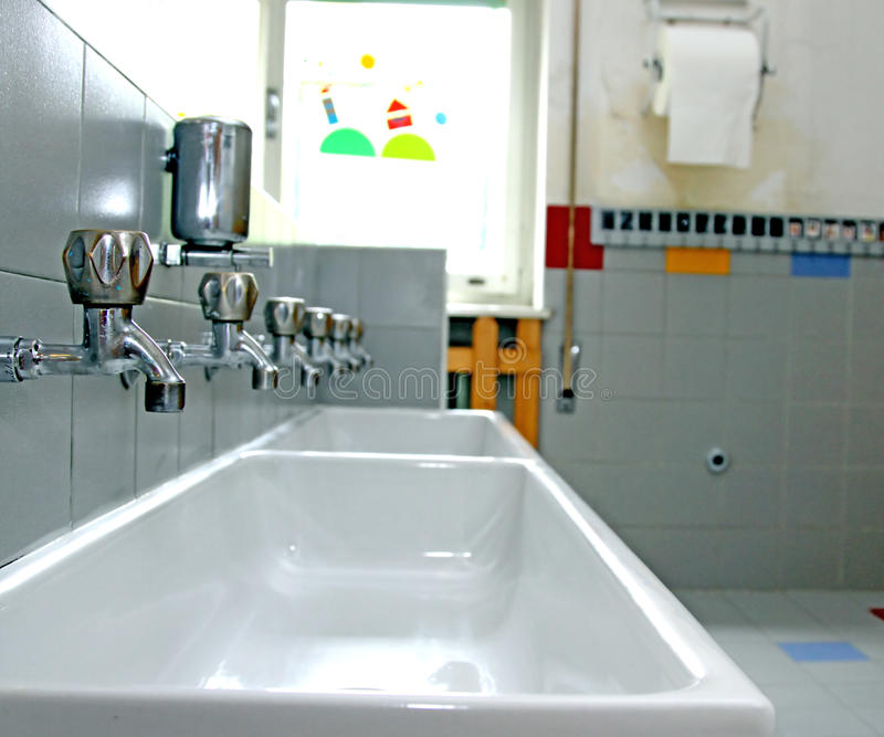 Very low taps in the toilets of a nursery. Sinks and washbasins with very low taps in the toilets of a nursery stock image