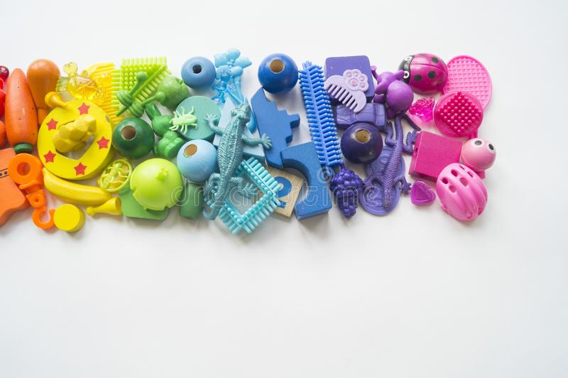 Rows of colorful rainbow toy bears.Very many kids toys rainbow color.Kids toys frame on white background. Top view. Flat lay. Very many kids toys rainbow color stock image
