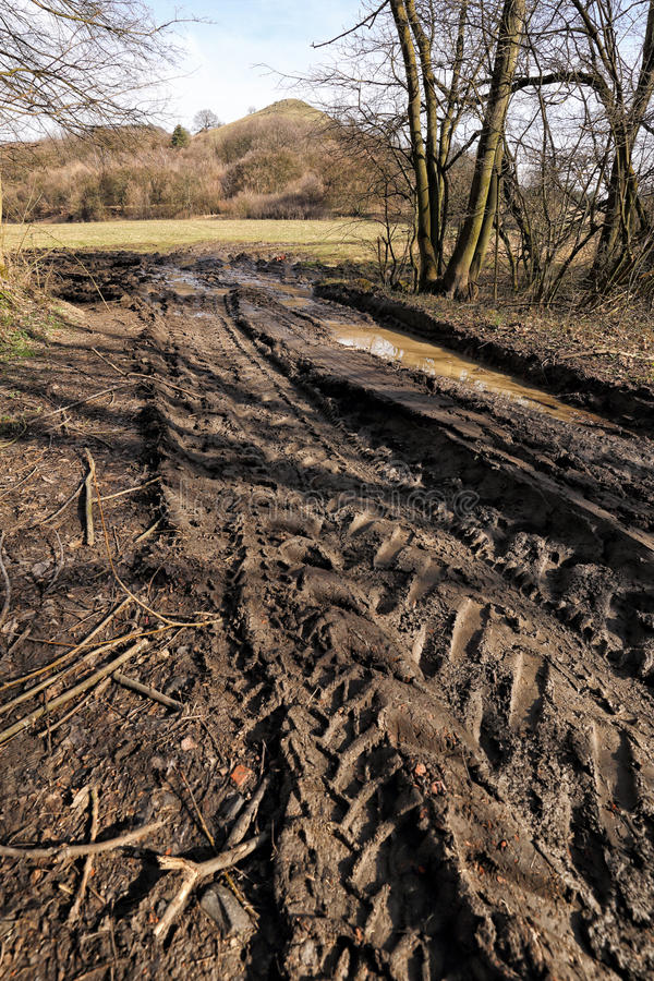 Very muddy rural road with the tractor traces stock image