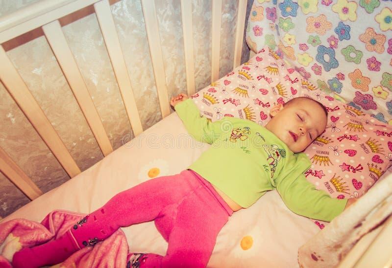 Very nice sweet baby sleeping in crib stock photography