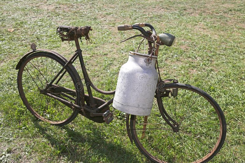 Old bicycle with aluminum milk bin to carry milk royalty free stock image