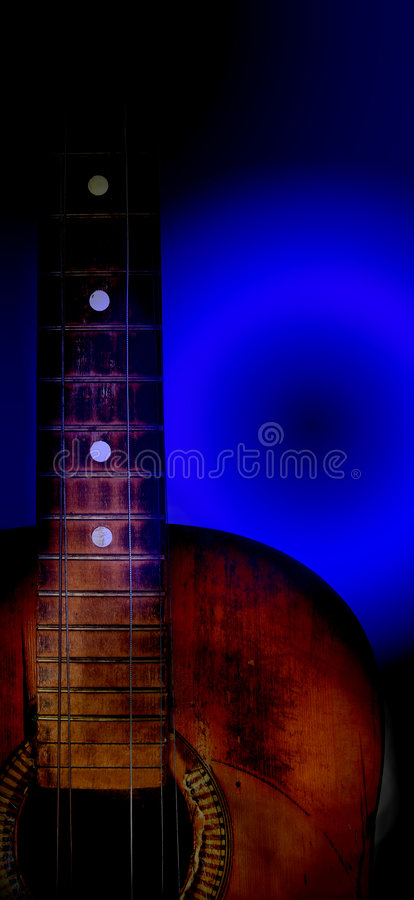 Very old blues guitar. In dark blue royalty free stock photo
