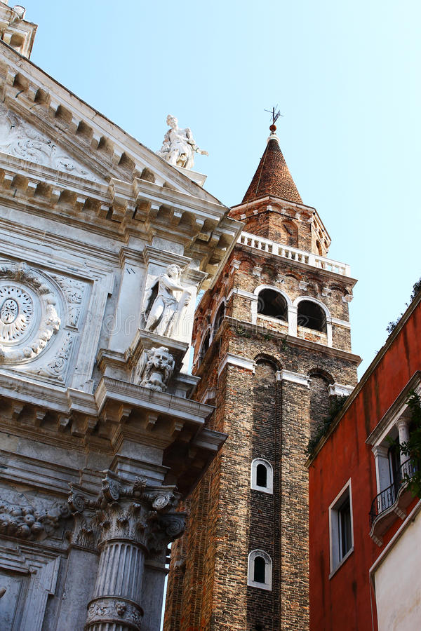 Very old buildings crowded inside Venice. Details of different buildings from Venice: old church, bricks tower and old building on the side stock images