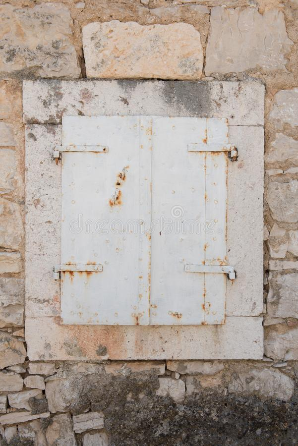 Very old closed window with white wooden shutters. Window with stone frame on a stone house. stock images