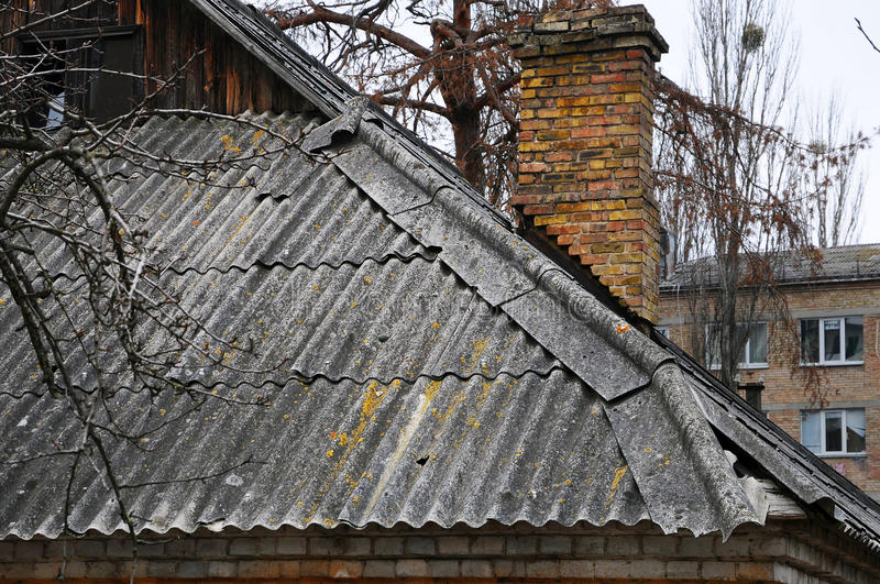 Very old damaged asbestos slate roof and chimney royalty free stock images