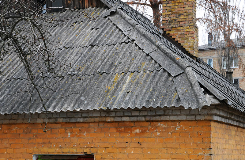 Very old damaged asbestos slate roof and chimney stock photos