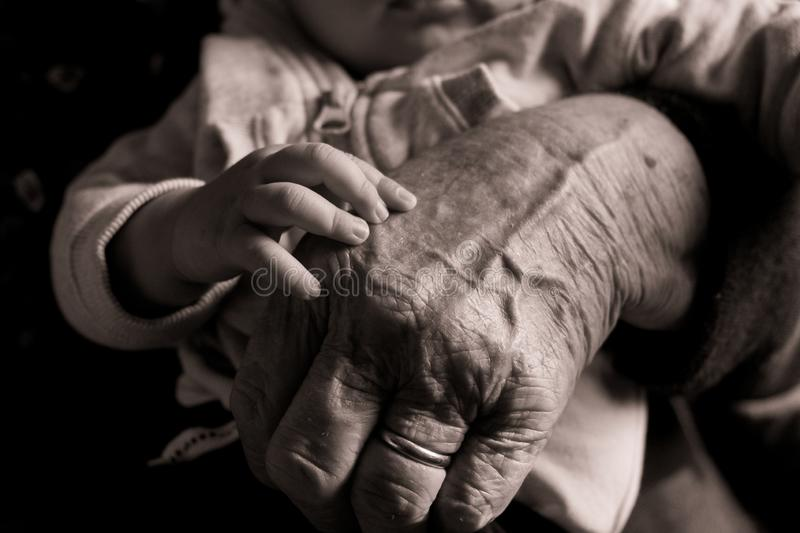 Small baby hand touching and caressing old grandmother hand with wrinkles, symbol of passing generations stock photos