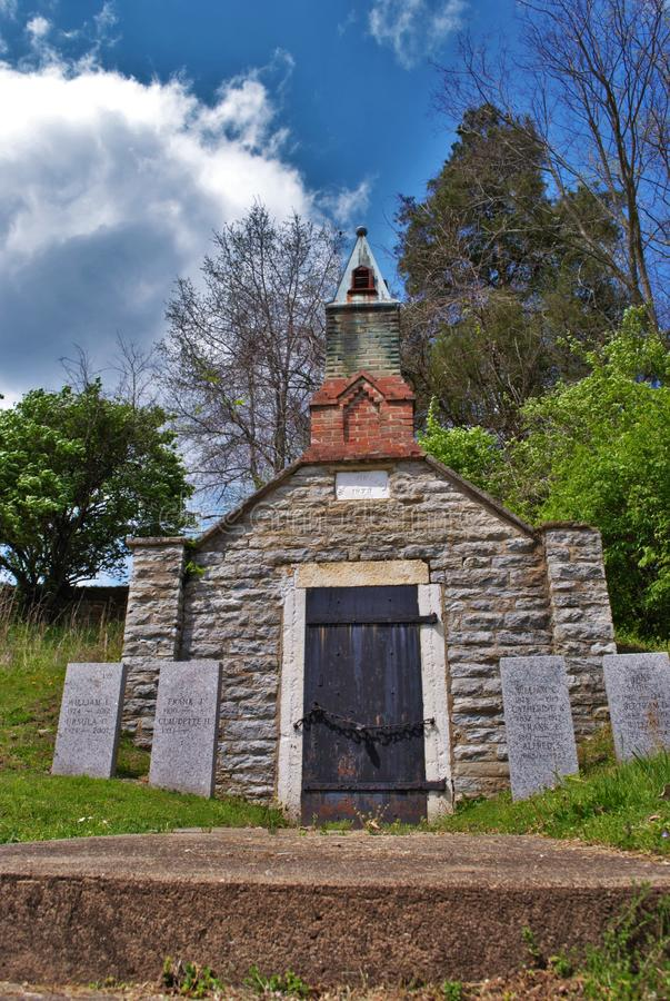 Very old mausoleum built into the side of a hill with steeple, tombstones, and wrought iron fence stock photos
