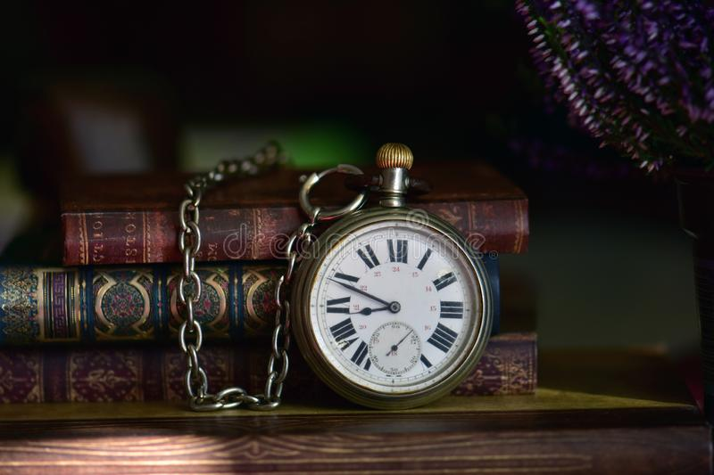 Very old pocket watch with chain and books stock photos