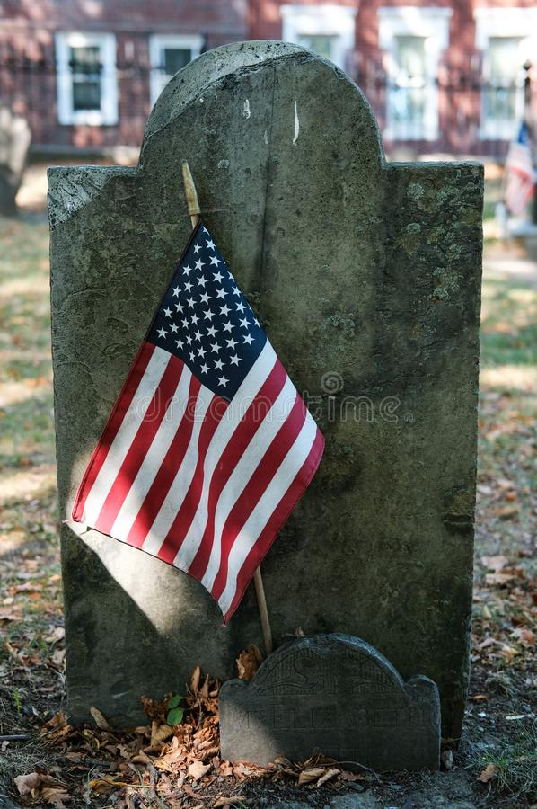 American civil war gravestone with the US flag in Boston, MA. Very old slate type gravestone with a smaller gravestone in front, seen with a planted US flag in royalty free stock photo
