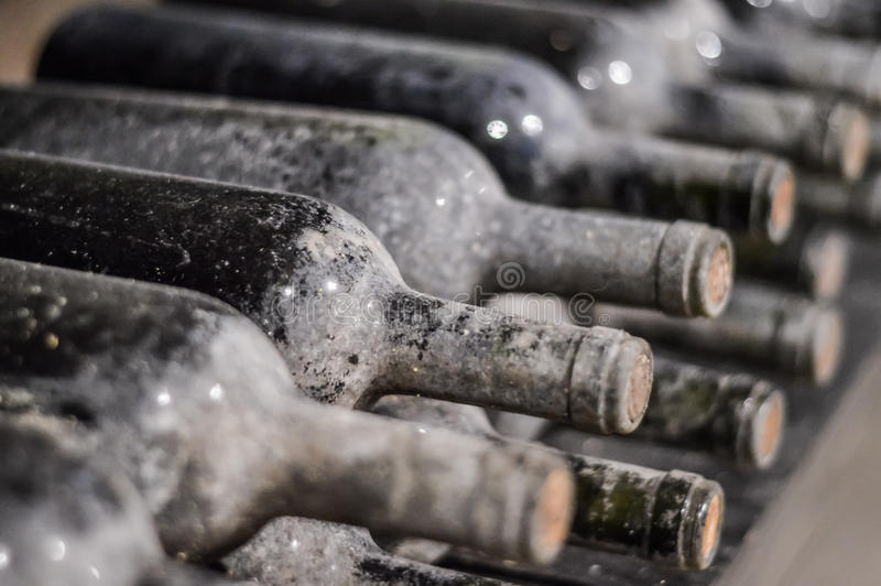 Very old stacked wine bottles stock image