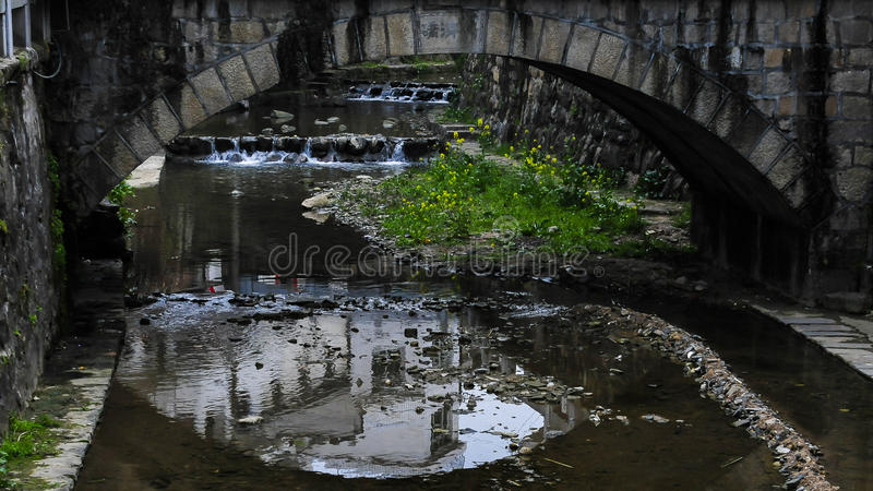 Very old stone bridge over the quiet lake with its reflection in the water royalty free stock image