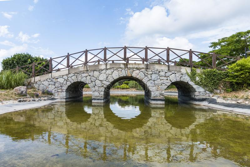 Very old stone bridge over the quiet lake with its reflection in the water royalty free stock photo