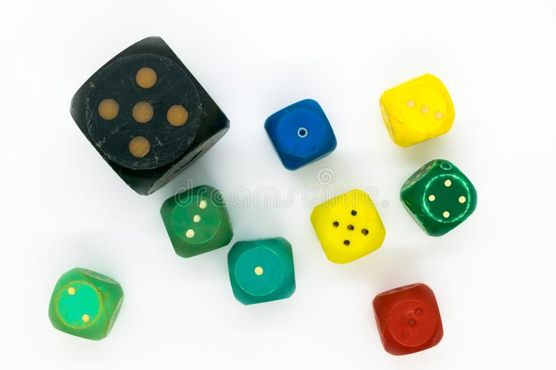 Very old and various colors plastic gaming dice on white background surface.  royalty free stock image