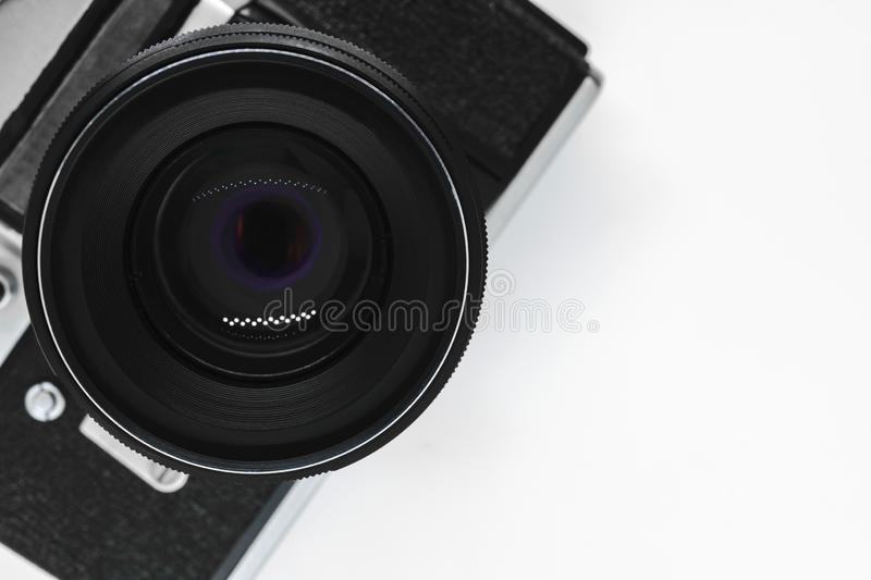 Very old vintage SLR black photo camera with black lens view from top with copy space and white background stock photos