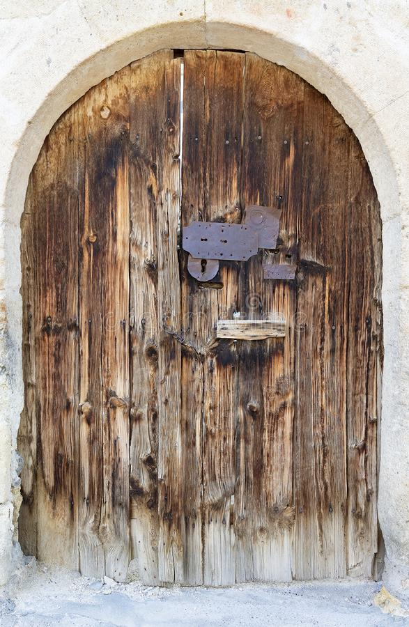 Ancient arched antique wooden doors with a metal lock in the middle stock images
