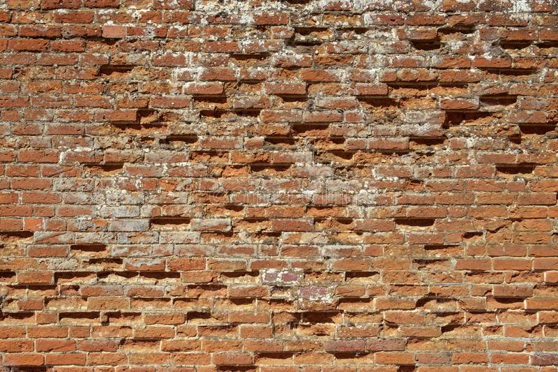 Very old weathered, damaged, badly repaired red brick wall stock image