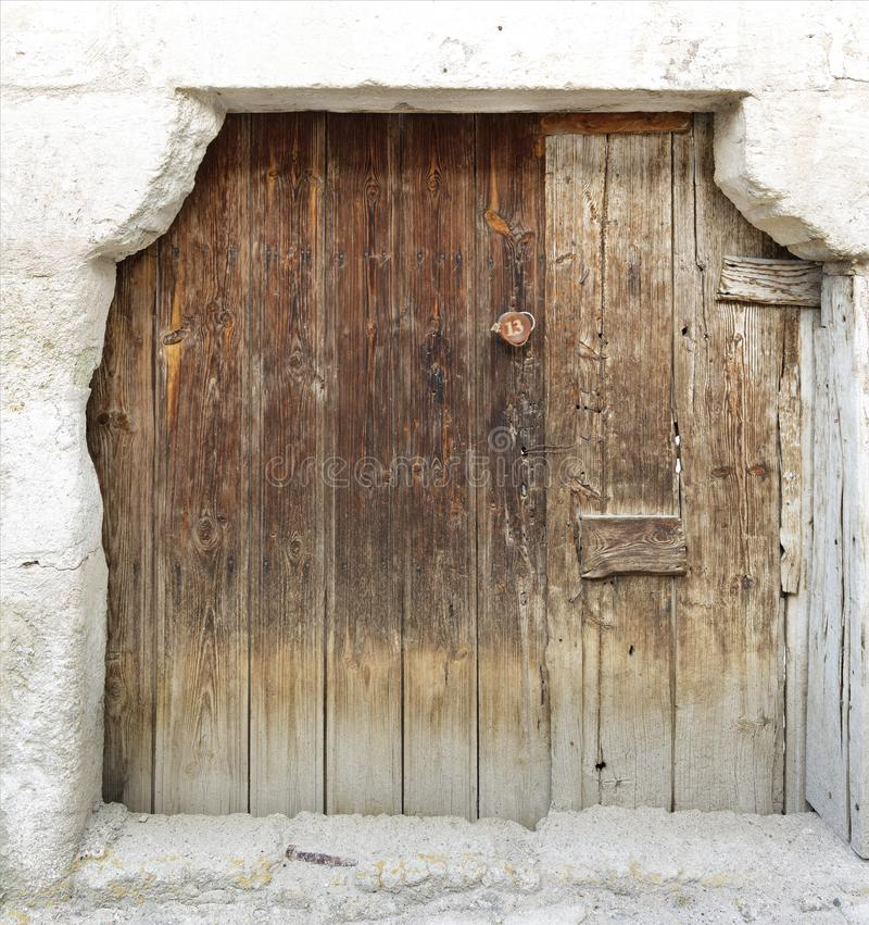 Ancient trapezoidal antique wooden doors with a wooden lock in the middle royalty free stock image