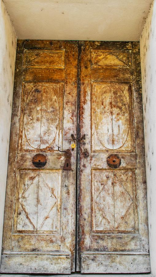 A very old wooden door. Entrance to a three-century old building. Rusty chain and lock royalty free stock image