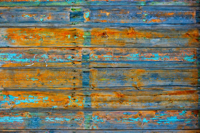 Very old wooden fence in rural area with footprints of blue paint and bright orange colored wood surface stock image