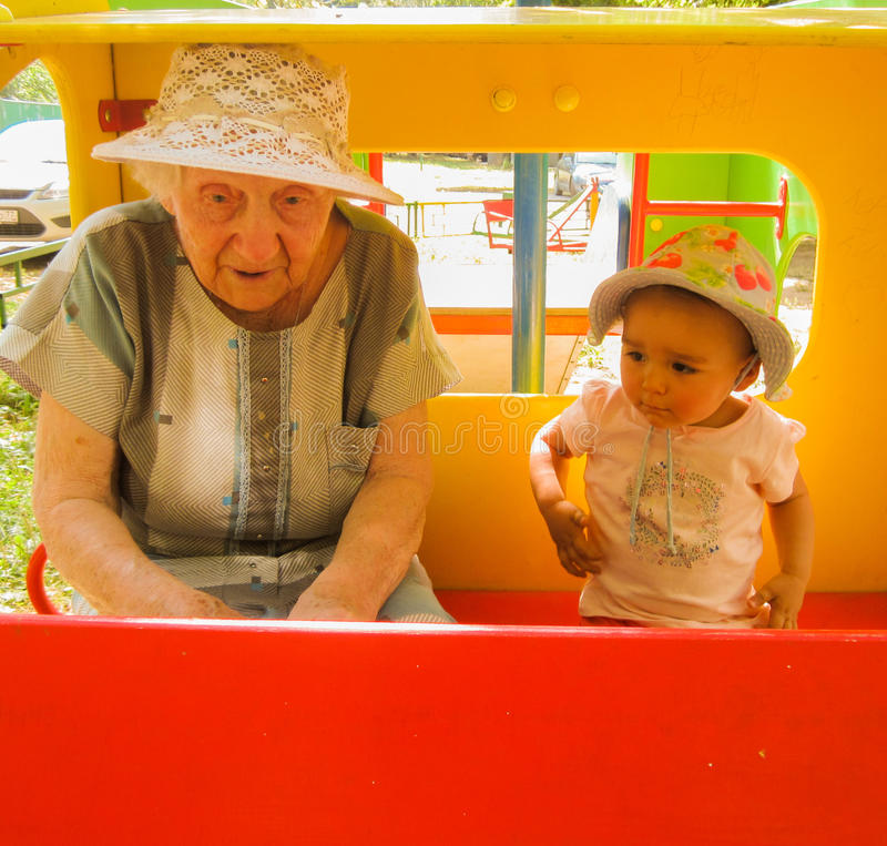 Very older grandmother talking with her little granddaughter on playground, both wearing bonnets, red blank board. Photo took in Moscow, Russian royalty free stock photography