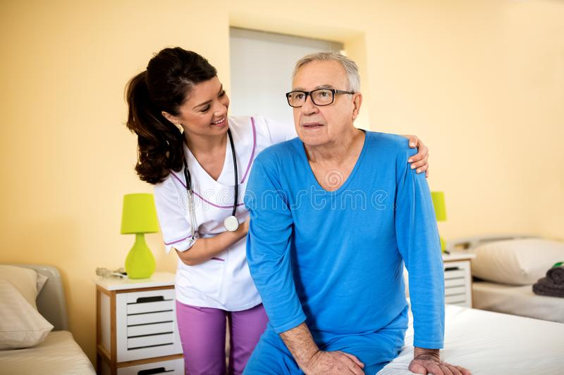 Very patient nurse helps old senior man to stand up from bed royalty free stock images
