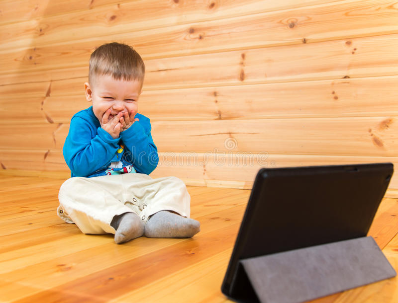 Very pleased little boy enjoying watching his tablet computer royalty free stock photo