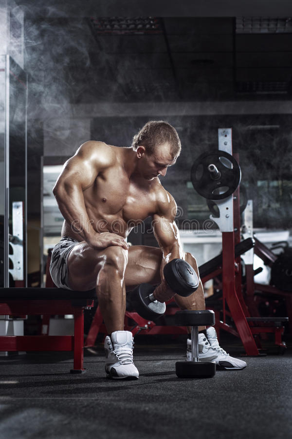 very power athletic guy , execute exercise press with dumbbells, workout in sport hall royalty free stock image
