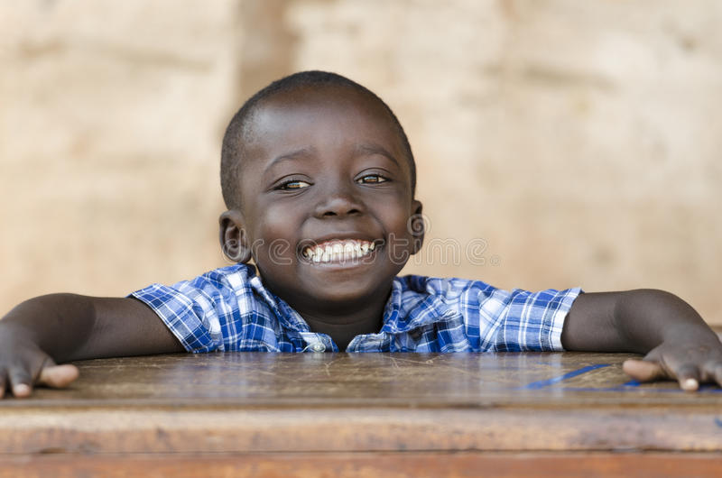 Very Proud Black African Boy Posing Under The Sun. Education symbol, little African kid smiling happily sitting in his desk. royalty free stock photo