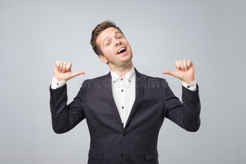 Very proud man shows his fingers on himself standong isolated on lgray background. stock photo