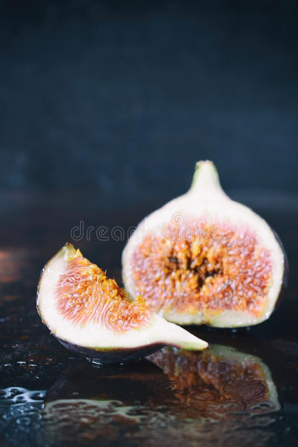 A very ripe blue fig on a dark background. Organic fruits. Healthy food royalty free stock photography
